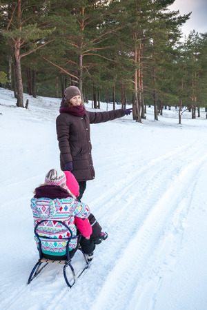 Caucasian family on the winter walking. Mother pulls sled with her two daughters photo