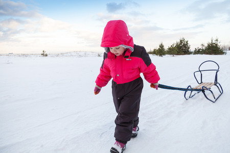 Little baby girl in pink pulling a sled on snowy winter road photo