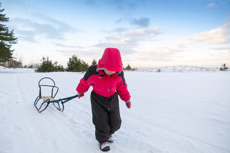 Little baby girl in pink pulling a sled on snowy road photo