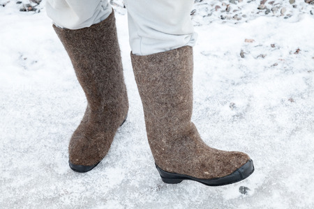 valenki: Male feet with Russian felt boots on winter road with snow and ice Stock Photo