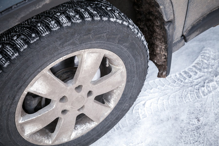 Modern automotive wheel with studded tires and winter snowy road photo