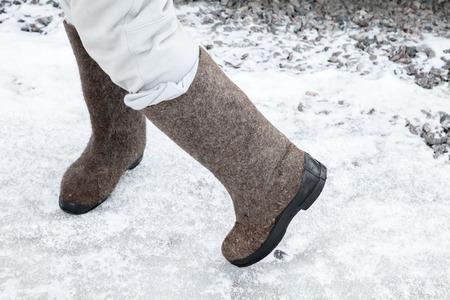 pies bailando: Pies bailando con botas de fieltro tradicionales rusas en invierno carretera nevada