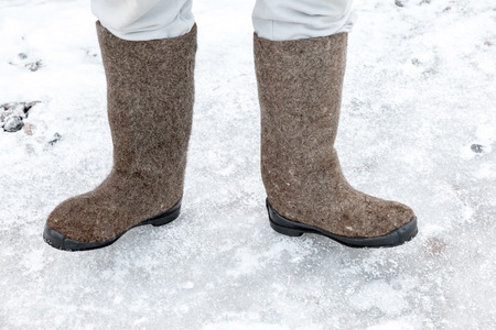 valenki: Male feet with traditional Russian felt boots on winter snowy road