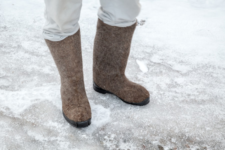 valenki: Feet with traditional Russian felt boots on winter road with snow and ice