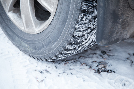 Fragment of automotive wheel with studded tires and winter snowy road photo