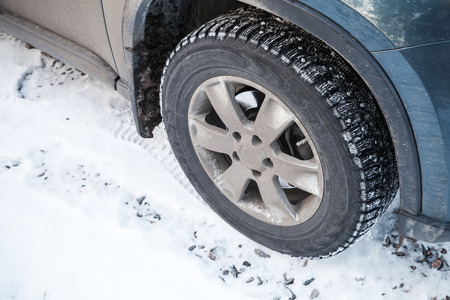 Modern automotive wheel with studded tires and winter road photo