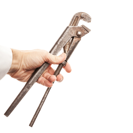 Old rusted screw wrench in male hand isolated on white background photo
