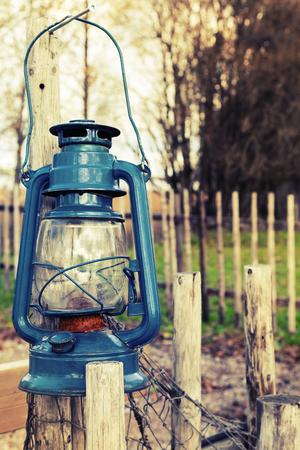 candil: Antigua lámpara de queroseno azul cuelga en la cerca de madera al aire libre, tonos foto vintage con efecto de filtro