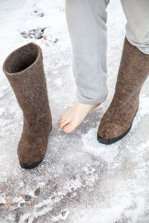 valenki: Male feet with traditional Russian gray felt boots stand on icy road