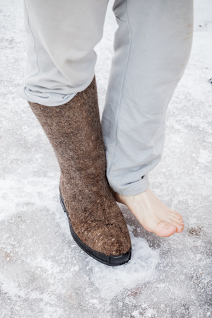 valenki: Male feet with one traditional Russian gray felt boot stand on icy road