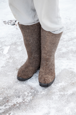 valenki: Feet with traditional Russian gray felt boots stand on winter road with snow and ice