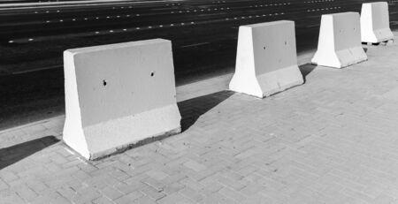 roadside stand: Road barrier. White concrete blocks stand on urban roadside