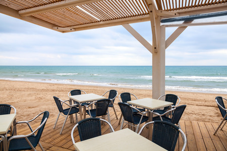 Open space seaside bar interior with wooden floor, roof and metal armchairs on the sandy beach photo