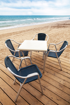 Open space seaside bar interior with wooden floor and metal armchairs on the sandy beach photo