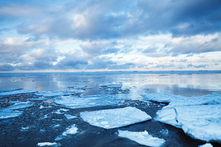 Winter coastal landscape with floating ice on deep blue sea water. Gulf of Finland, Russia