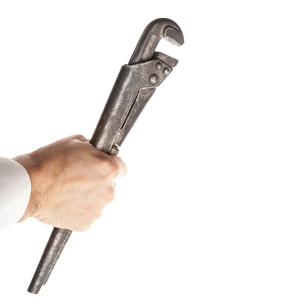 Old rusted steel screw wrench in male hand isolated on white background photo