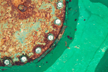 Old green grunge metal plate with rusted cover and bolts, background photo texture photo