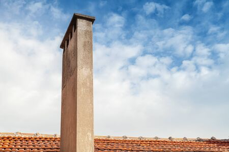 tall chimney: Tall chimney on red tile roof with cloudy sky background Stock Photo
