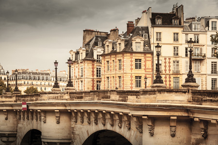 dark street: Pont Neuf vintage stylized photo with filter effect. The oldest bridge across the Seine river in Paris, France