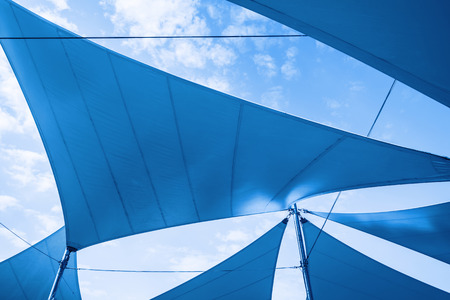 blue and white: Awnings in sails shape over cloudy sky background. Blue toned photo