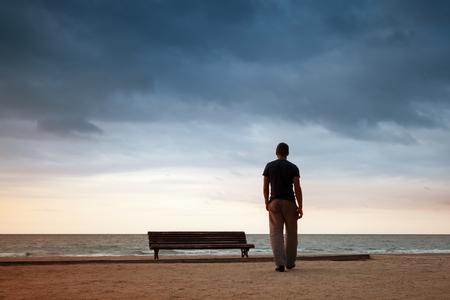 muž: Člověk jde na břehu moře poblíž staré dřevěné prázdné lavici. Vintage osočil fotografie s retro tónování efektu filtru