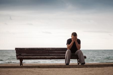 hombre solo: Hombre triste que se sienta en el viejo banco de madera en la costa del mar. Vintage enton� la foto con efecto de filtro tonificaci�n retro