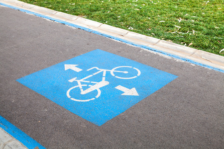 Bicycle lane. Blue and white road marking over urban asphalt road and green grass Stock Photo
