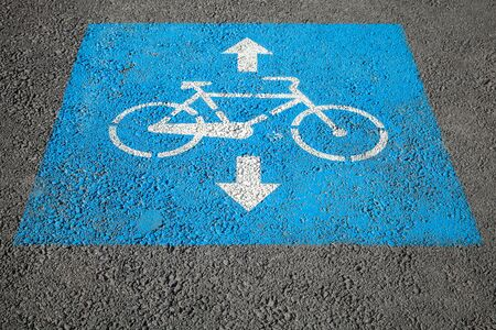 road marking: Bicycle lane. Blue and white road marking over urban asphalt road Stock Photo
