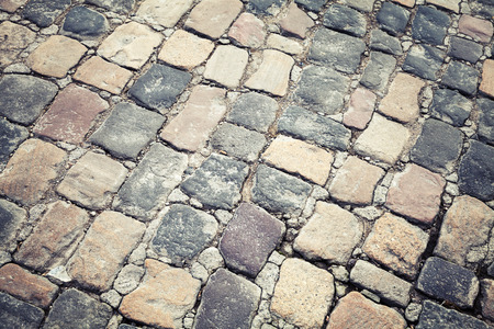 Old stone road pavement, background texture. Vintage toned photo with retro filter effect photo
