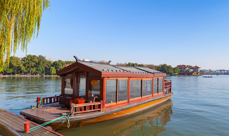 Traditional Chinese red wooden water taxi boat stands moored on the West Lake coast. Famous park in Hangzhou city center, China 版權商用圖片