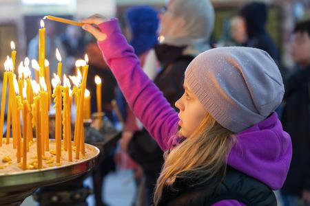 family praying: Niña rubia caucásica con velas en la Iglesia Ortodoxa Foto de archivo