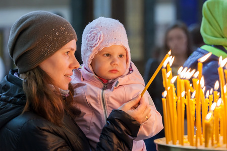 church interior: Young mother and her little blond Caucasian daughter with candles in Orthodox Russian Church