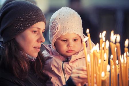 familia en la iglesia: Madre y peque�a hija de raza cauc�sica rubia con velas en la Iglesia Ortodoxa Rusa. Filtro retro vintage foto correcci�n tonal Foto de archivo