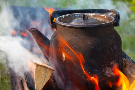 Bonfire with metal old black boiling teapot on it photo
