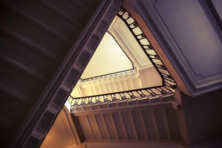 stairs interior: Abstract interior fragment, triangle shaped flight of stairs, looking up. Vintage toned photo with old style filter effect