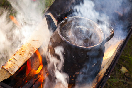 Bonfire with smoke over metal old black boiling teapot photo
