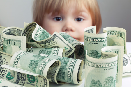 banco dinero: Pila de los Estados Unidos de d�lar cientos de d�lares billetes en el cuadro blanco y el beb� borrosa buscando en ella en un segundo plano. Efecto de filtro Retro tonal de correcci�n de fotos, enfoque selectivo en dinero