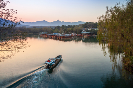 boatman: Small Chinese fishing boat with boatman goes to the West Lake coast. Famous park in Hangzhou city center, China Stock Photo