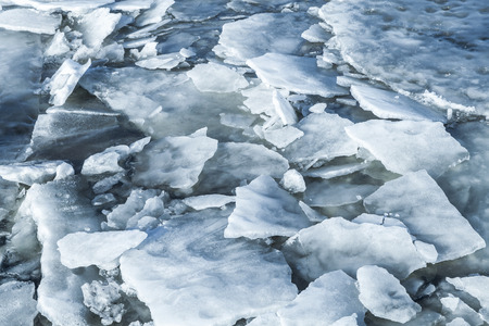 fragments: Big ice fragments covered with show on frozen river water. Dark blue natural background