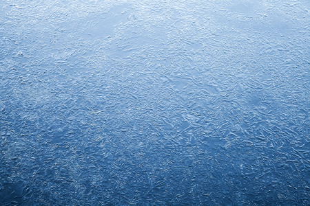Thin ice layer of frozen river water. Dark blue natural background texture