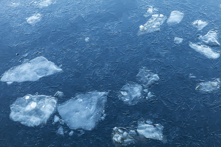 fragments: Ice fragments under thin layer of frozen river water. Dark blue natural background Stock Photo