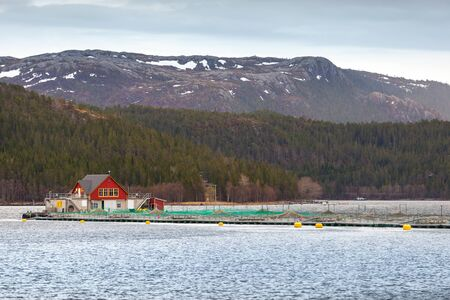 salmon fishery: Traditional Norwegian floating fish farm with red wooden house and nets Stock Photo