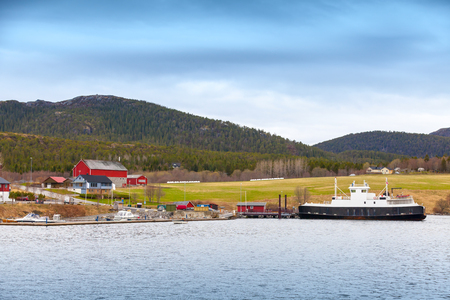 Traditional Norwegian small village with colorful wooden houses and ferry photo