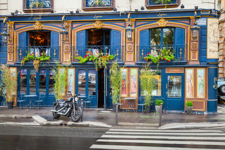 green street sign: Paris, France - August 07, 2014: Black motorcycle stands parked near blue bar facade on the Quai Des Grands Augustins Editorial