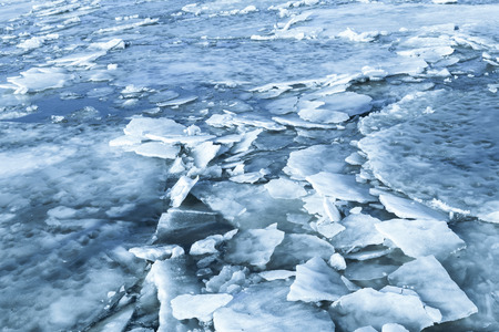 fragments: Big ice fragments covered with show on frozen river water. Dark blue nature background Stock Photo