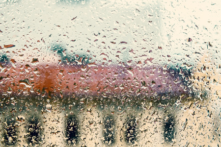 tonal: Rainy background with flowing down water drops on window glass, vintage toned photo with tonal filter effect Stock Photo