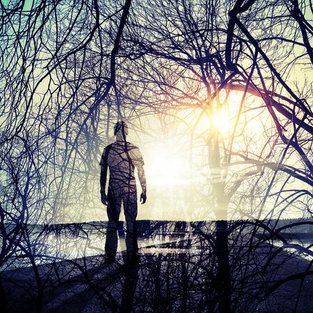 hombre solo: Doble exposición conceptual abstracto collage de fotos, hombre de pie en la costa, brillante patrón de sol y ramas de los árboles