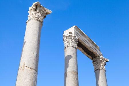 portico: Ancient columns and portico fragment on blue sky background, fragment of ruined roman temple in Smyrna. Izmir, Turkey
