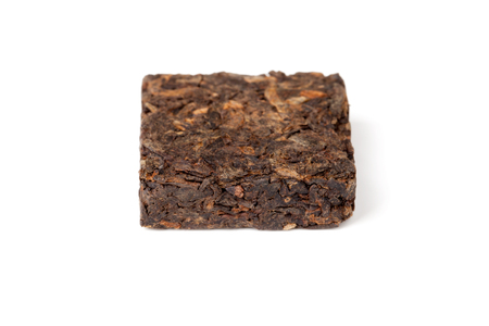 shu: Small pressing square briquette of black Chinese Shu Pu-erh tea isolated on white background