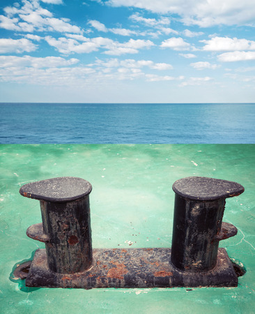 ship deck: Old black rusted bollard mounted on green ship deck, with sea landscape on a background Stock Photo